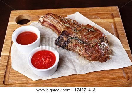 ribeye steak on a wooden board with pita bread and sauce