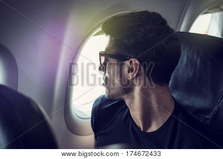 Side view of handsome young man against plane window sitting and looking out