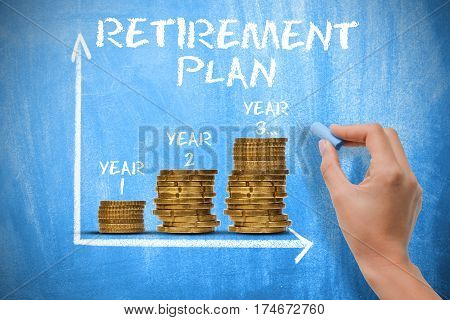 Retirement plan concept with piles of coins on blue chalkboard