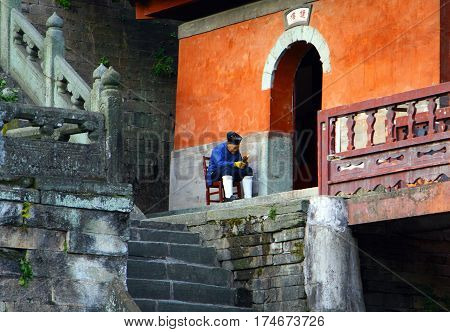 Wudangshan, China - Nov 8, 2007: Elderly Taoist Monk Sitting At The Entrance To Purple Cloud Temple
