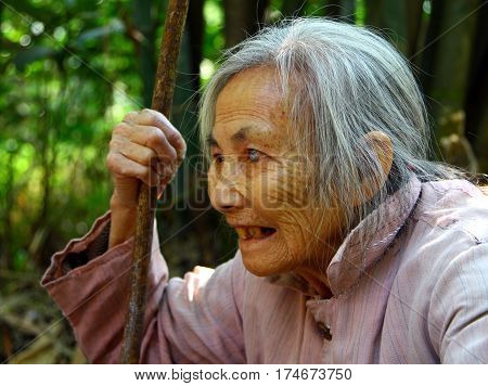 Guilin, Guangxi Province, China - Nov 6, 2007:  Elderly Chinese Woman With A Staff In Her Hand. In R