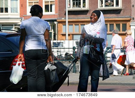 Amsterdam, Netherlands - Jul 4, 2009: Two Smiling African Black Women Speaking On The Street. Amster