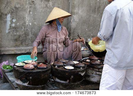 Phan Tiet, Viet Nam - Feb 10, 2009: Vietnamese Woman On The Street Market Selling Snacks, Heated On