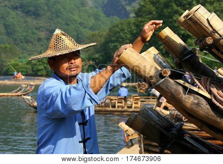 WUYISHAN, FUJIAN, CHINA - OCT 20, 2009: Chinese man preparing bamboo rafts to travel on the River of Nine Bends. Bamboo rafting is very popular tourist attraction in the scenic area of Wuyi mountains