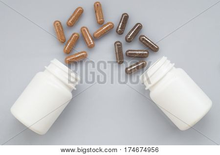 Medicinal capsule spill out of a two plastic bottles on a light surface