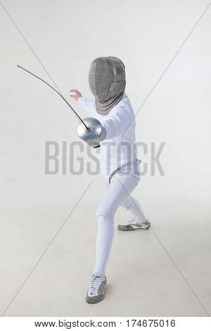 Female fencer wearing white fencing costume isolated on white background