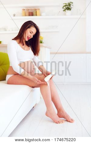 beautiful pregnant woman applying cream on swelling feet