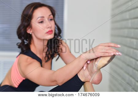 Ballerina stretches herself near barre in the classroom, focus on feet, shallow depth of field.