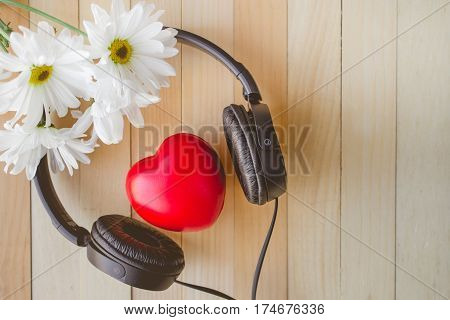 Relaxation and cozy with Heart listen music and Daisy on wooden background and copy space for love and music concept