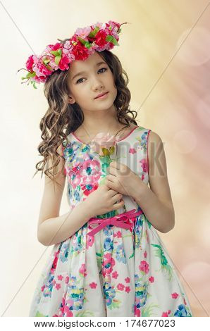 Portrait Of Cute Little Girl In Nice Spring Dress, With Flower Wreath On Head, Holds Pink Rose In Ha
