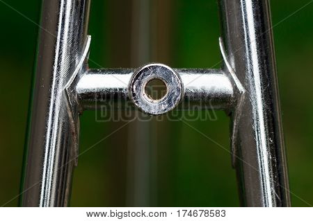 Bicycle frame part detail from top stay brake holder made of silver chromed metal pipe tubes on a blur green background