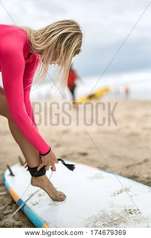 Blonde girl fixates the mount on her leg on the surfboard on the beach on the blurry background of the sky and the ocean. She wears pink swimsuit. Closeup. Vertical.