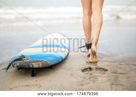 Female legs with a colorful surfboard on the sand on the blurry background of the ocean waves and the sky. Board  fixates on the left leg with the rope and the mount. Closeup. Horizontal.
