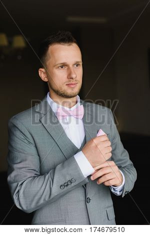 Elegant young fashion man dressing up for wedding celebration. Handsome groom dressed in modern gray suit white shirt and pink bow tie getting ready for event. Groom buttoning a shirt.