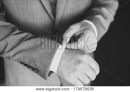 Elegant young fashion man dressing up for wedding celebration. Color close up image of male hands. Groom buttoning a shirt. Dark background. Black and white photo