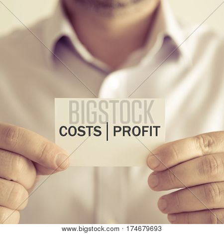 Businessman Holding Costs Profit Message Card
