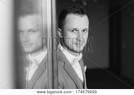 Elegant young fashion man dressing up for wedding celebration. Portrait of young man wearing bow tie and suit. Groom silhouette reflected in the window. Black and white photo.