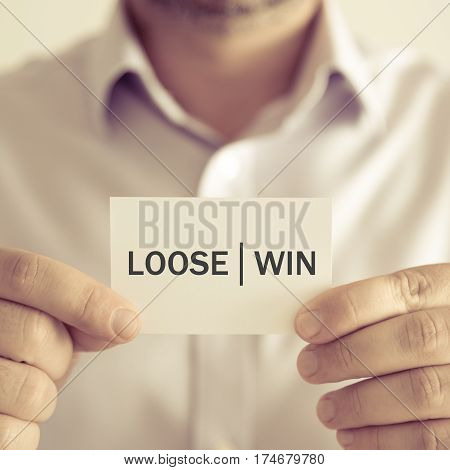 Businessman Holding Loose Win Message Card