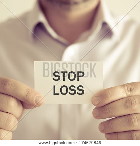 Businessman Holding Stop Loss Message Card