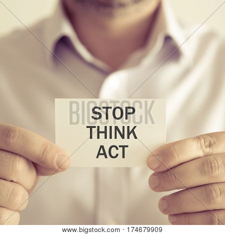 Businessman Holding Stop Think Act Message Card