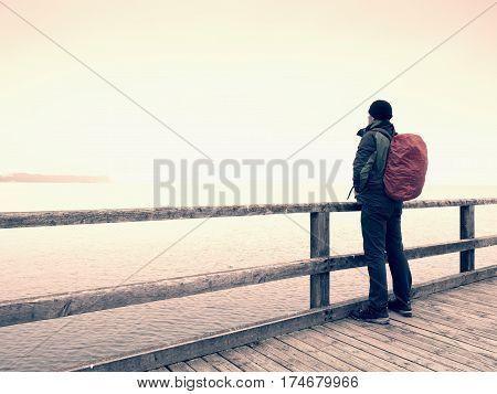 Man Tourist  At End Of Wooden Sea Pier. Cold   Autumn Mist