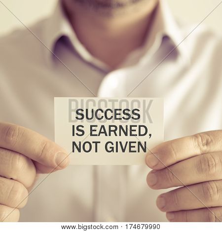 Businessman Holding Success Is Earned, Not Given Message Card