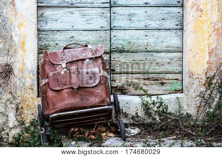 Old vintage retro leather brown suitcase on wheels abandonedon on a doorstep of old antique ruined house in front of wooden door as a romantic travel station or memory and reminiscence concept background