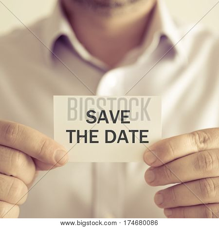Businessman Holding Save The Date Message Card