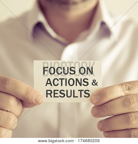 Businessman Holding Focus On Actions And Results Message Card