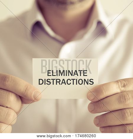 Businessman Holding Eliminate Distractions Message Card