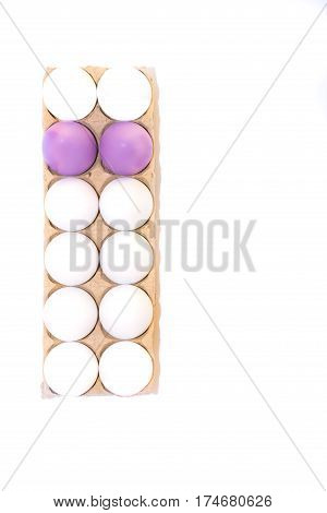 Two Easter eggs dyed lavender and ten white hard boiled hen's eggs in a cardboard carton photographed from above against a white background with copy space.