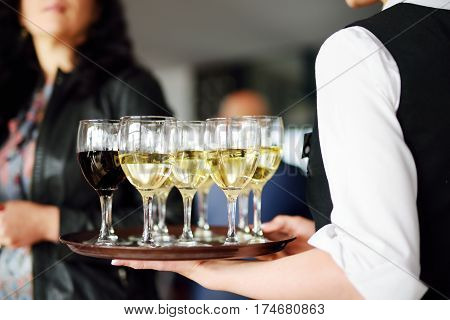 Waitress Holding A Dish Of Champagne And Wine Glasses At Festive Event