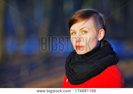 Portrait of young cute girl with a stylish haircut in a red coat and black scarf at the neck posing in the bright sun on a blurred background of trees in the Park closeup.
