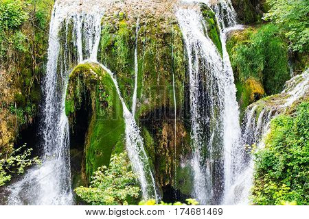 River falls in spring flowing over the green moss and algae in bright sunny day as waterfall and fresh white clear water background
