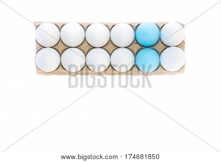 Two Easter eggs dyed blue and ten white hard boiled hen's eggs in a cardboard carton photographed from above against a white background with copy space.