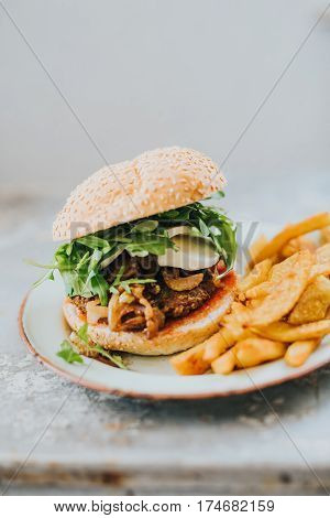 Homemade veggie burger and fries made without oil on a metal plate