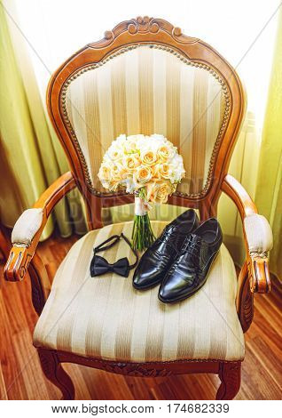 wedding bouquet with groom's black shoes and bow tie lying on chair near window.