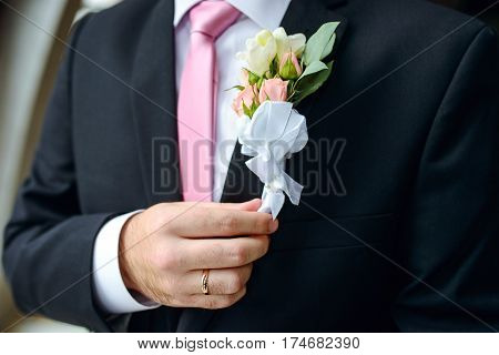 elegant groom holding hand near buttonhole flowers. closeup shot