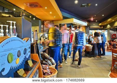 timisoara romania - april 6 2014: people inside the starbucks coffeeshop in timisoara romania. shot taken on april 6th 2014
