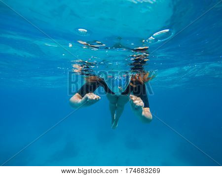Woman swimming in blue water. Beautiful woman under water before dive to coral reef. Half snorkel woman face in mask. Tropical sea snorkeling. Summer vacation activity. Woman snorkeling in blue ocean