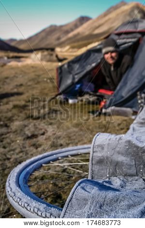 man walking up and looking from his tent on a frozen wheels of his bicycle while on cycle touring trip in yunnan province, china