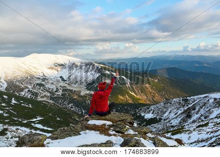 A tourist girl sits on a big gray stone and looks dreamily at mountains with snowy peaks and blue sky on a winter day.