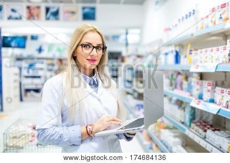 Pharmacist Using Modern Laptop And Internet Technology In Pharmacy Drugstore