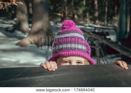 Cute young caucasian girl peeking from behind a bench in a park in winter