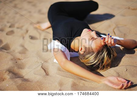 Pretty young girl relaxing lying on the sand his hands behind his head