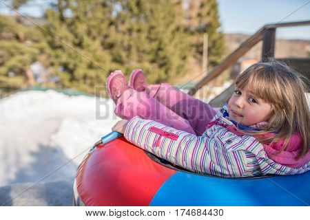 Little girl ready to slide downhill a snowy and icy hill track on a colorful inflatable tube