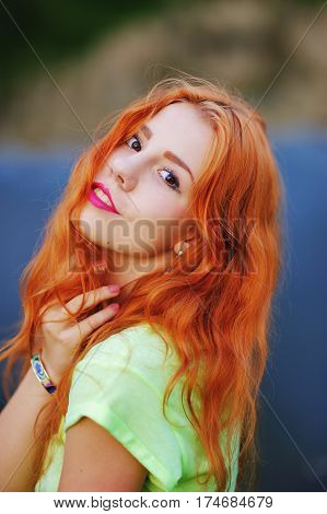 Portrait of a very beautiful brown eyed girls with bright red hair in a light green dress on a background of lake close-up