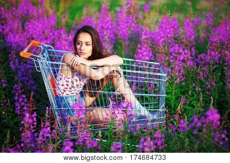 Wonderful portrait beautiful pensive long-haired brown-haired woman posing in supermarkets trolley in a flowered field. Girl dressed in a white t-shirt and shorts sitting under bright sun among purple flowers of fireweed