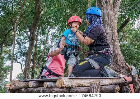 Labuan,Malaysia-Feb 12,2017:Happy kid with safety harness before playing on a flying fox in Labuan,Malaysia.There will be more ziplines in Malaysia,especially when there have so much natural resources & rainforest.
