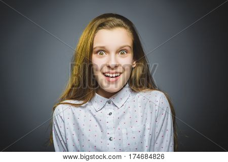wondering girl. Closeup Portrait of handsome teen in casual shirt on grey background.